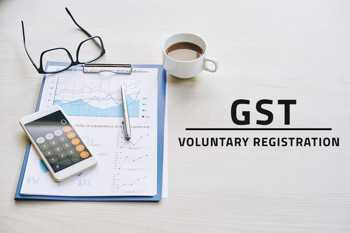 black text saying GST voluntary registration overlaying a white background with various items on a desk including black glasses, a filled coffee cup, a business financial report and a smartphone opened to a calculator app