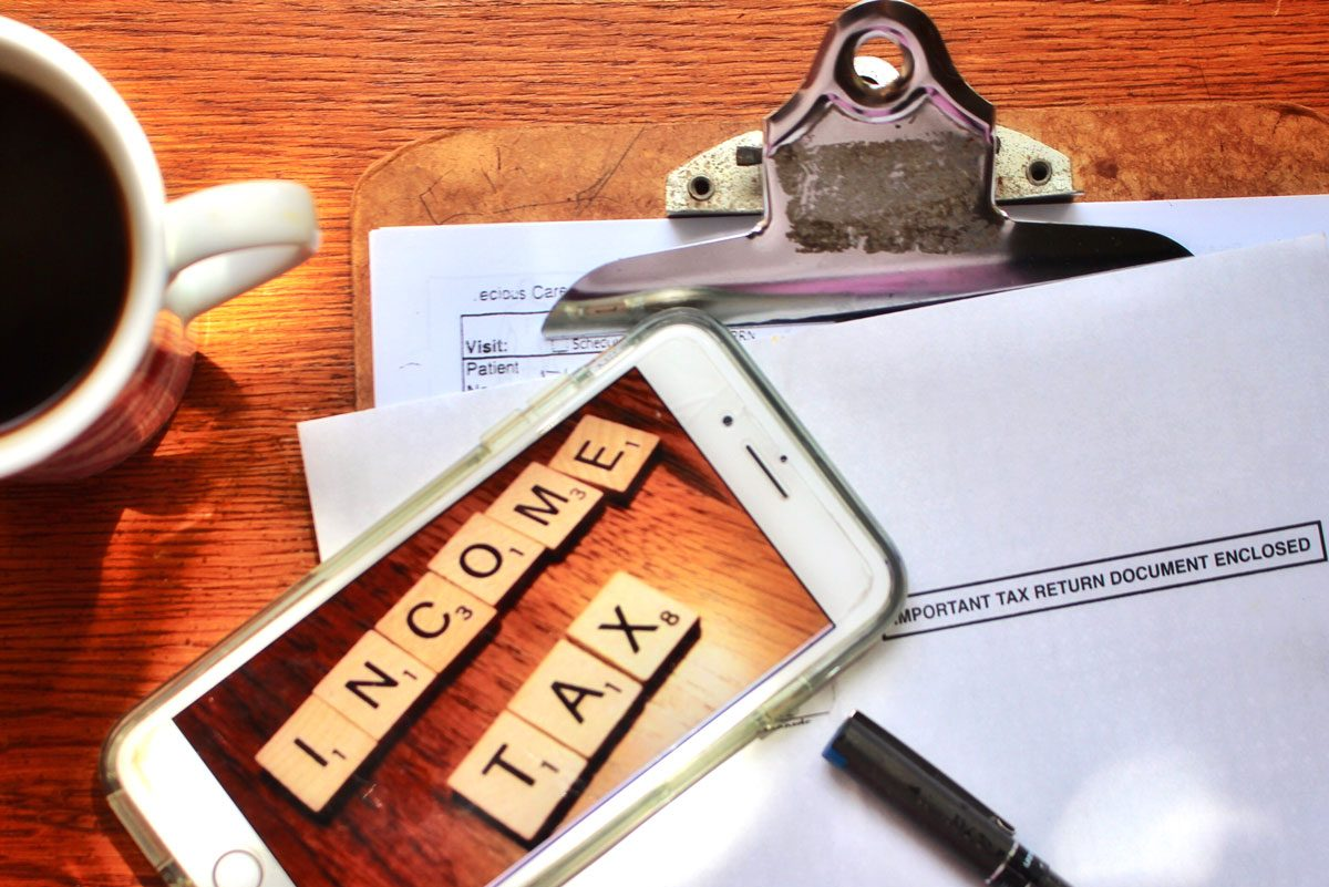 items on a desk: iras tax filing papers, coffee mug and a mobile phone showing image of tiles spelling income tax