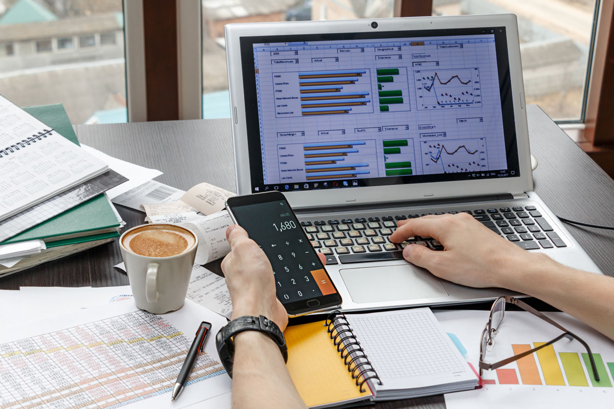 accountant holding a calculator and preparing income tax calculations for submission to IRAS, various tax documents and coffee mug on desk