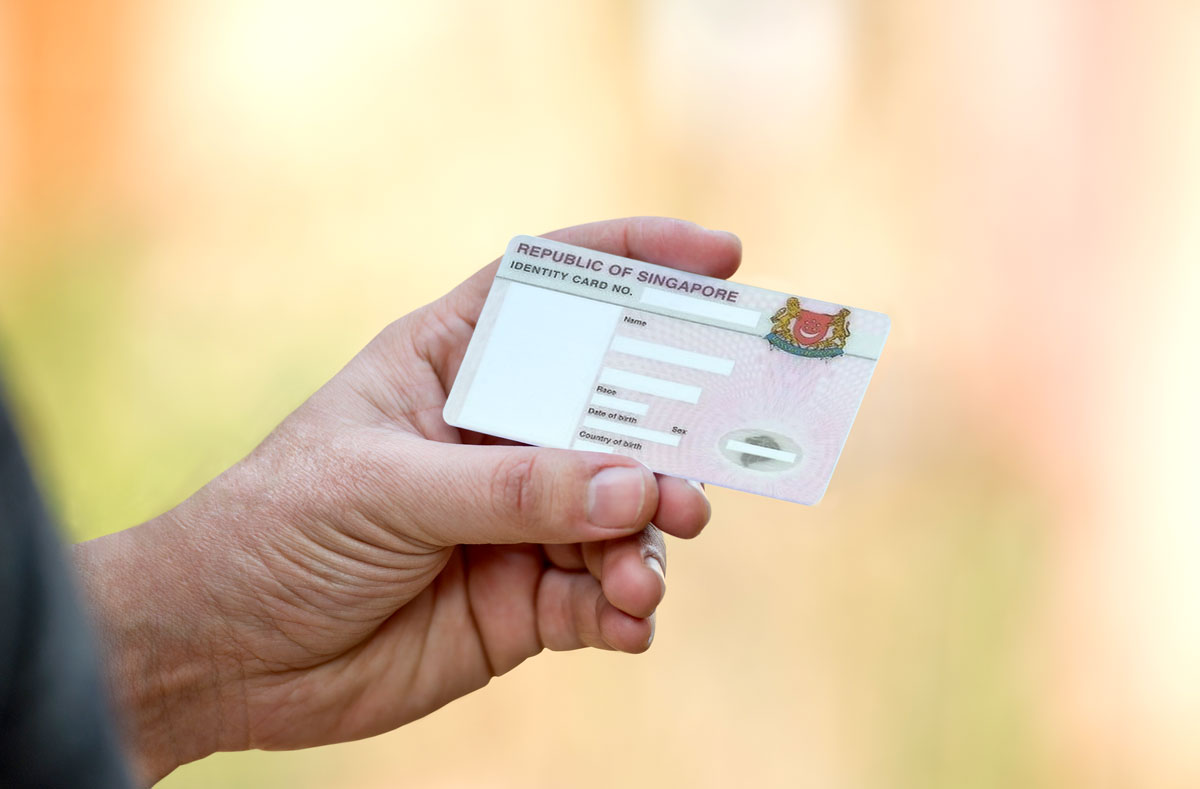 man's hand holding an NRIC which serves as a valid Singapore tax identification number