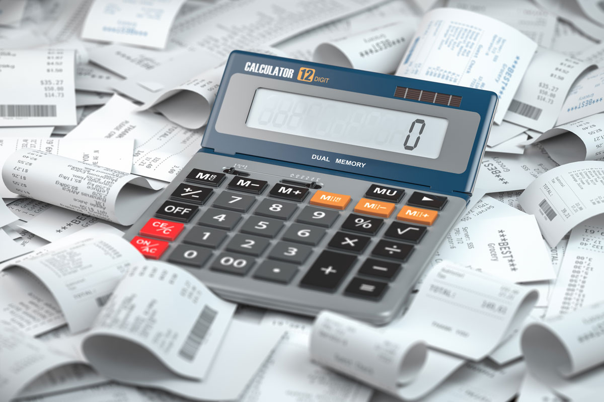 calculator on top of a pile of receipts showing vat taxes