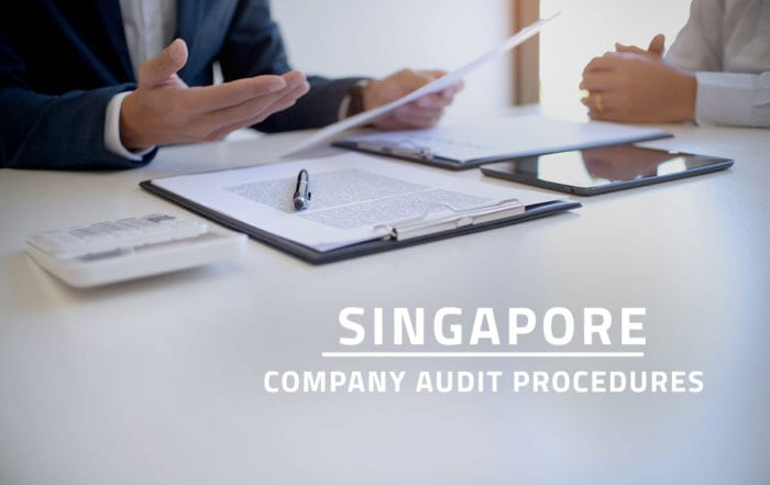 words Singapore company audit procedures overlaying background showing company auditor or internal revenue staff discussing company financial statements