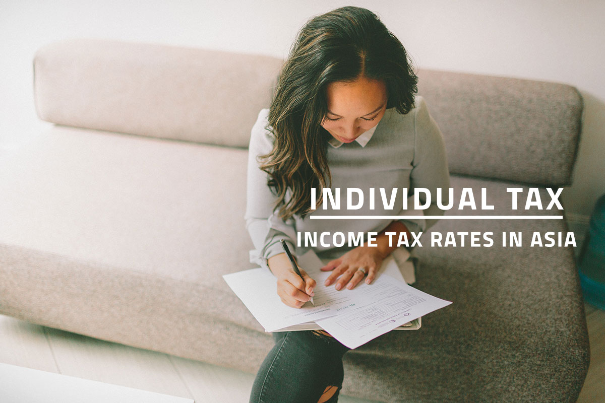 words individual tax income tax rates in asia over background of woman reviewing her personal tax documents while seated on a couch