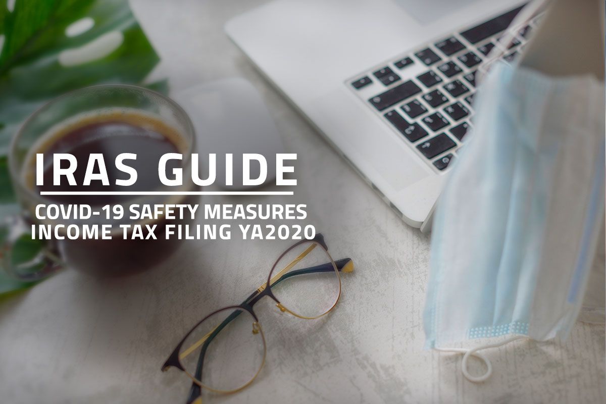 Words: IRAS Guide Covid-19 Safety Measures Income Tax Filing YA2020 against background of a coffee cup, glasses, laptop and a surgical face mask on a white table