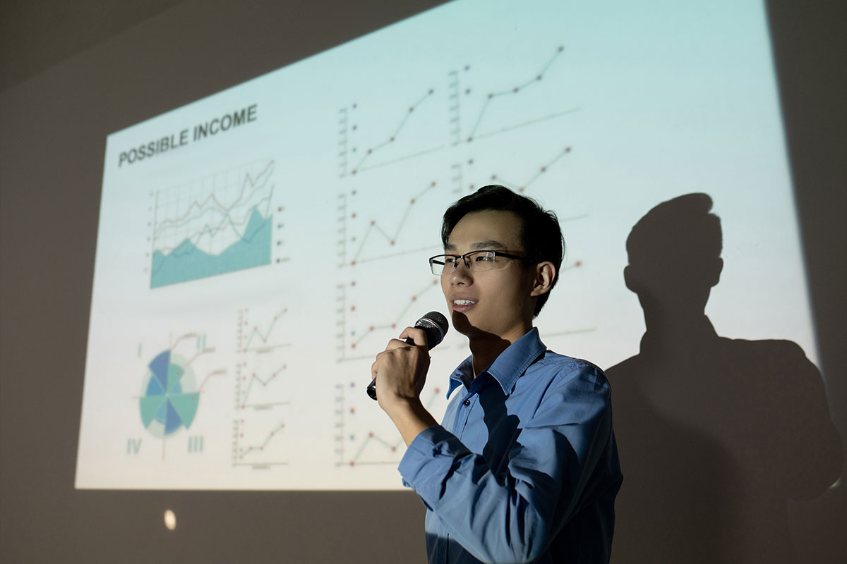 young asian man presenting business figures projected on a whiteboard