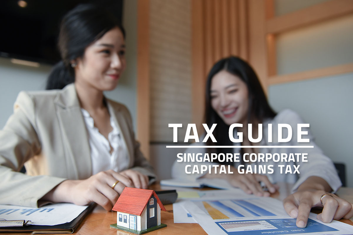 Words Tax Guide Singapore Corporate Capital Gains Tax against background of two asian employees discussing in an office. Accounting documents and a model house on a desk.