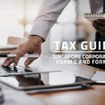 words tax guide Singapore corporate tax form c and form c-s against background of a corporate employee using a laptop on a desk